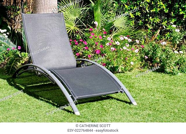 A sun lounger in a garden