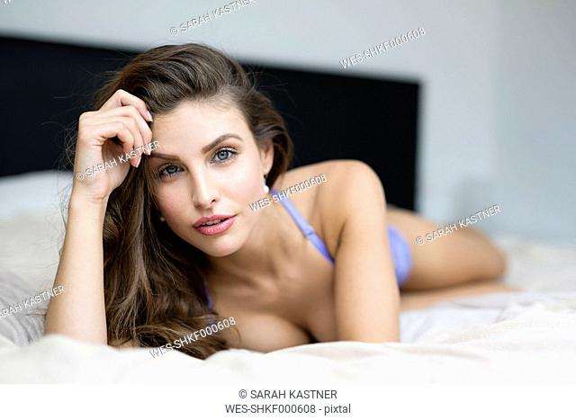 Woman in lingerie lying on bed