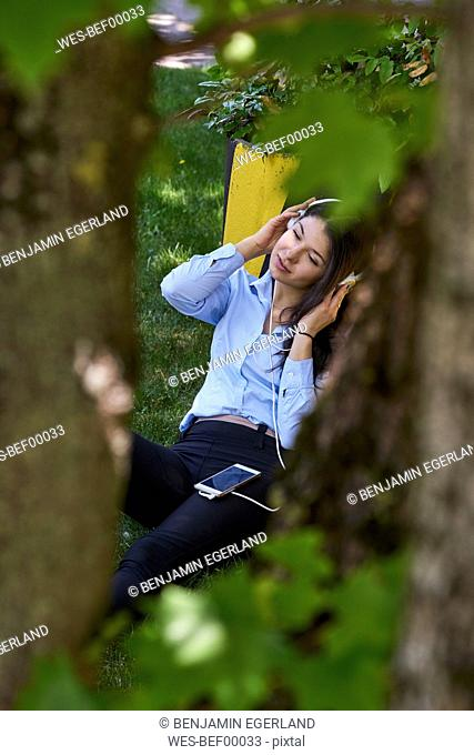 Young woman sitting on a meadow listening music with headphones and cell phone