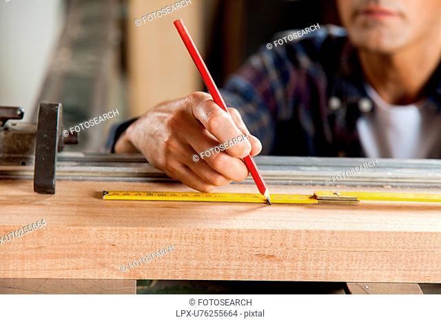 Serious carpenter marking a plank