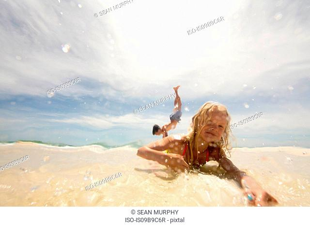 Girl lying on beach in shallow water, brother doing handstand in background