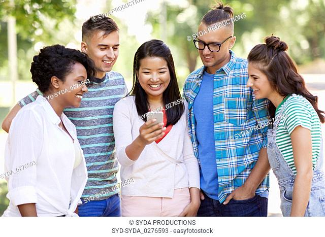 group of happy friends with smartphone outdoors