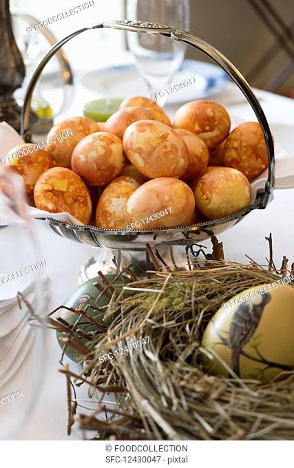 Brown coloured eggs in a silver dish behind a painted Easter egg in a straw nest
