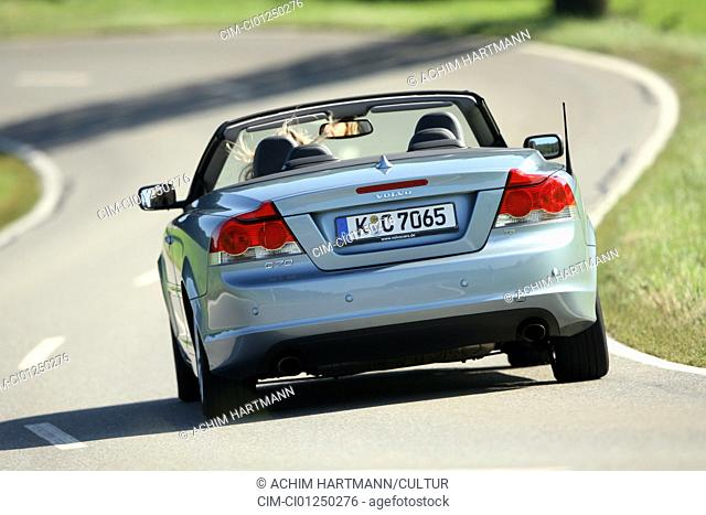 Volvo C70 T5 Summum, model year 2006-, silver, driving, diagonal from the back, rear view, country road, open top