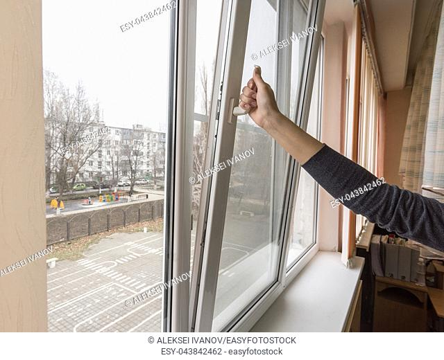 A hand opens a window to air the room