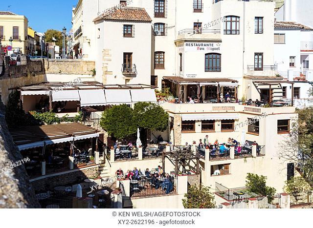 Ronda, Malaga Province, Andalusia, southern Spain. Diners enjoying winter sunshine at restaurants overlooking the Tajo gorge