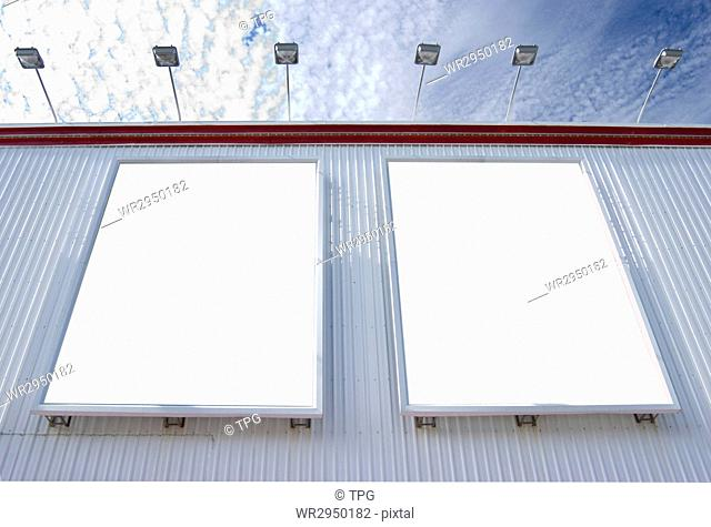 multiple blank billboard with lamps under sunny sky
