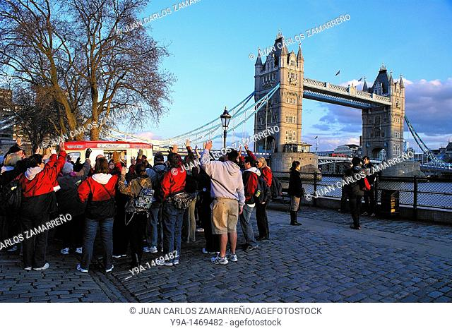 A tourist group hands in up in the dusk at the Tower Bridge of London,England