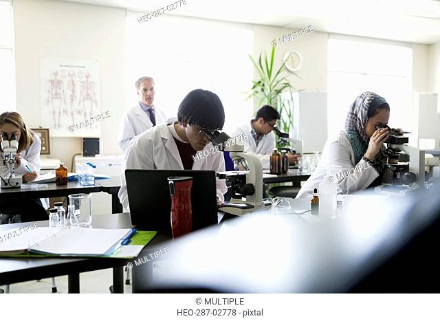 Professor and students at microscopes in science laboratory