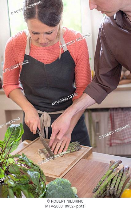 Couple cutting asparagus in kitchen