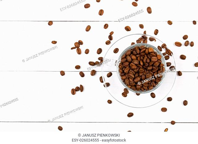 Coffee beans in the cup on a wooden background