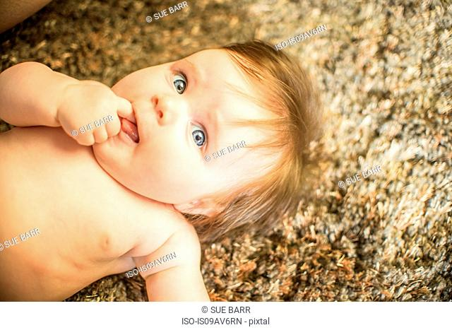 High angle view of baby girl lying on carpet, finger in mouth looking away