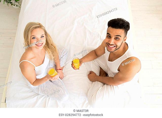 Young Couple Drink Orange Juice Sitting In Bed, Happy Smile Young Hispanic Man And Woman Top Angle View Lovers Hold Glasses Bedroom
