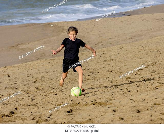 Girl chasing soccer ball across sand on shore at the beach