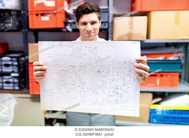 Man working on charts and plans in warehouse