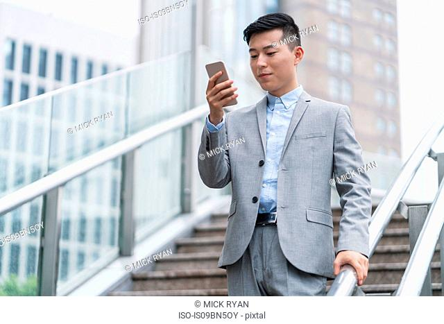 Young businessman looking at smartphone on city stairway, Shanghai, China
