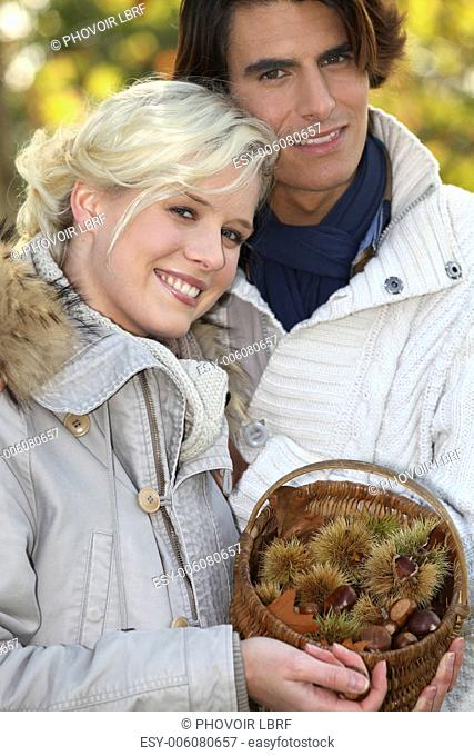 couple dressed in warm clothes, woman is holding a wickerwork basket full of chestnuts