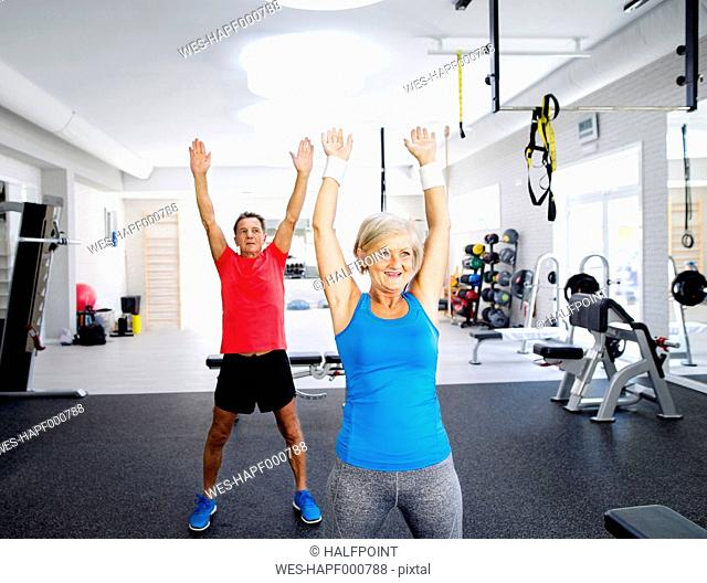 Mature woman and senior man doing gymnastics in fitness gym