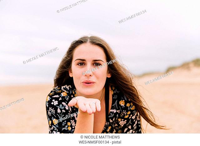 Portrait of young woman blowing kiss on the beach