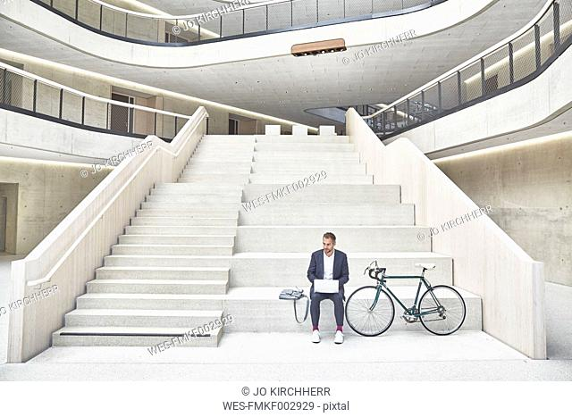 Businesssman on stairs using laptop next to bicycle
