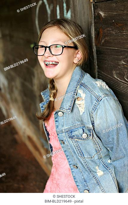 Smiling Caucasian girl leaning on wooden wall