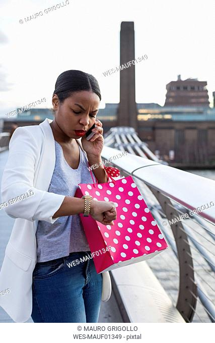 UK, London, woman on cell phone with shopping bags in the city checking the time