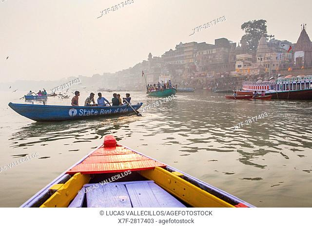 Pilgrims in a boats sailing and praying, Ganges river, in background the ghats, Varanasi, Uttar Pradesh, India