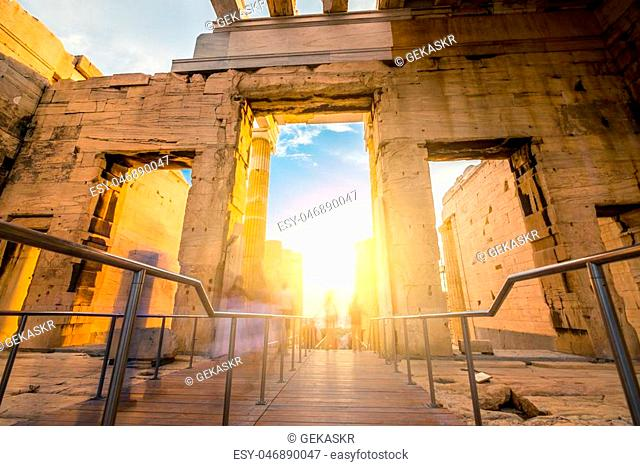 Motion blurred photo of tourists pass through the Propylaea monumental entrance to the Parthenon temple in Athens, Greece