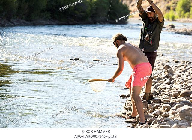 Two Friends Catching Fish At The Gros Ventre River In Jackson Hole, Wyoming