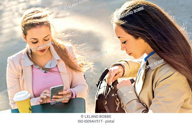 Young adult female twins reading smartphone texts at sidewalk cafe