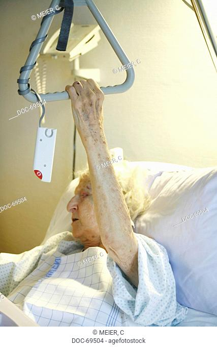 An elderly woman is lying in a sickbed and clinches her hand around its fixture