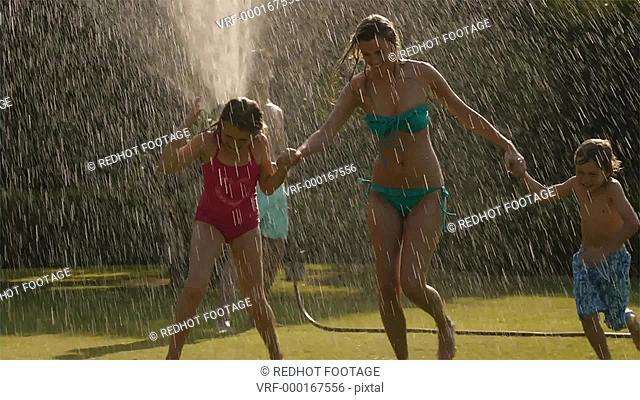 Slow motion shot of family playing in sprinkler, Sotogrande, Spain