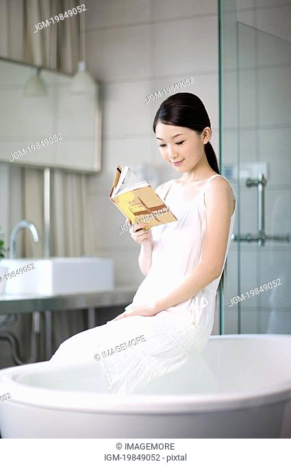 Young woman sitting on the bathtub and reading book