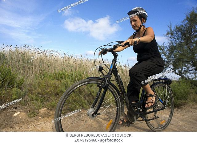 Woman riding in a bike. Pudent Lake. Formentera. Balearic Islands, Spain, Europe. Bicycle route