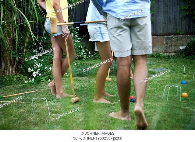 Teenagers playing croquet in garden, Sweden