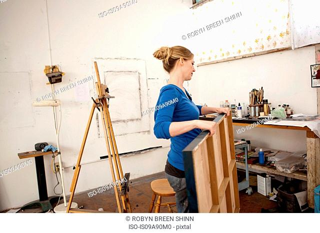Mid adult woman carrying oil painting in artist's studio