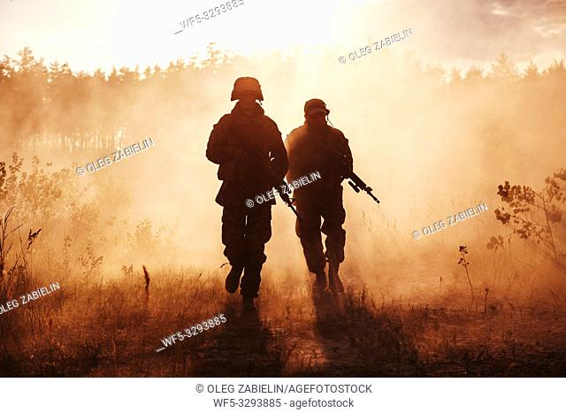 United States Marines in action. Military equipment, army helmet, warpaint, smoked dirty face, tactical gloves. Military action, desert battlefield