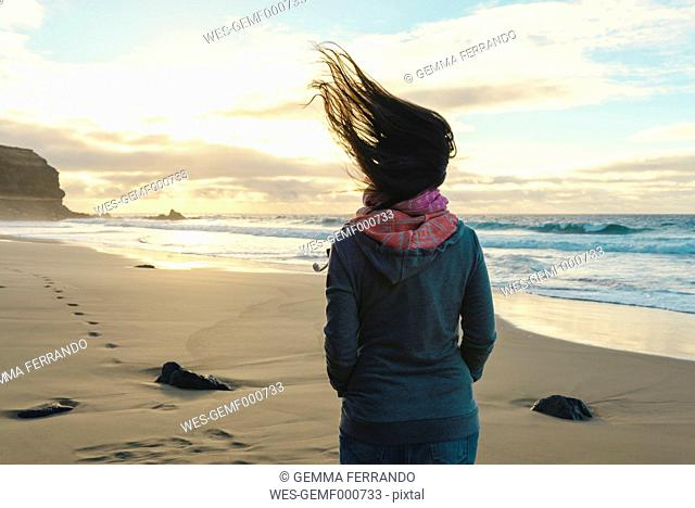 Spain, Fuerteventura, El Cotillo, back view of woman on the beach with blowing hair