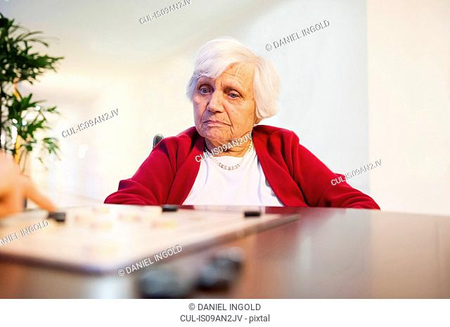 Senior woman playing board game at table