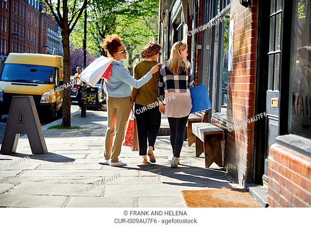 Rear view of women carrying shopping bags walking side by side in street looking through shop window
