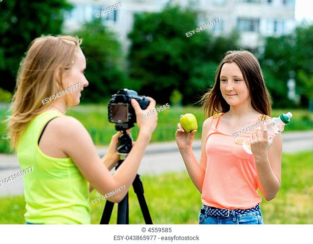 2 girls are teenagers. In the summer in park in nature. Writes the video to the camera. Here's how to hold an apple and a bottle of water