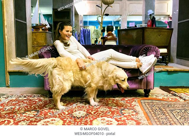 Smiling woman with dog lying on couch in a vintage shop