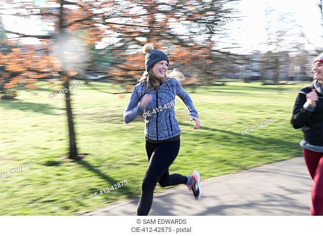 Smiling, confident female runner running in sunny park