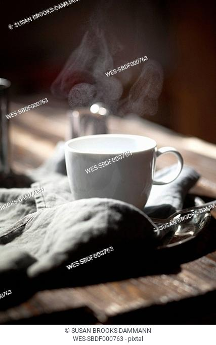 Cup of steaming tea on silver plate and wooden table