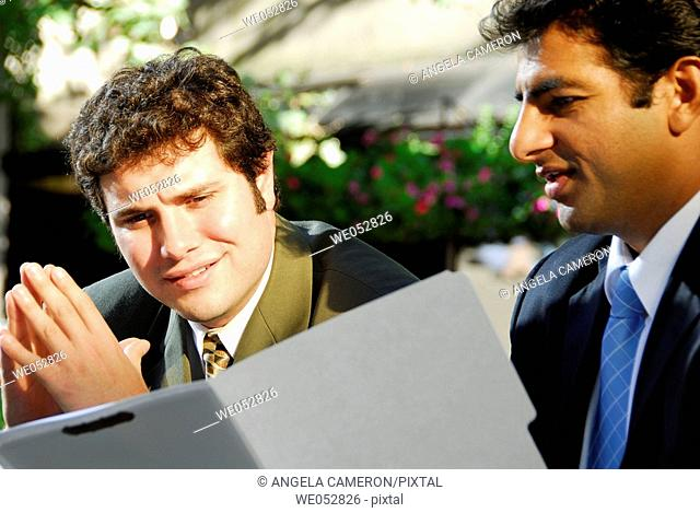 2 young male business men looking at file folder together