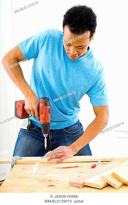 Mixed race carpenter using power drill
