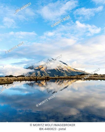 Reflection in Pouakai Tarn, stratovolcano Mount Taranaki or Mount Egmont with cloud, Egmont National Park, Taranaki, New Zealand