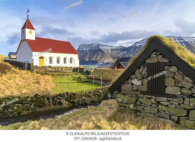 Stone hut with grass roof next to church of Mikladalur, Kalsoy island, Faroe Islands, Denmark