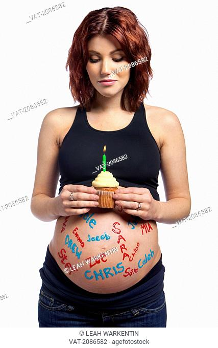 A pregnant woman with names written all over her bare belly holding a cupcake with a lit candle, edmonton alberta canada