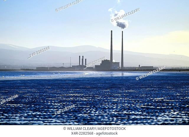 Poolbeg power station, Dublin, in the evening light, smoke billowing from the right cooling tower. Dollymount strand is in the foreground